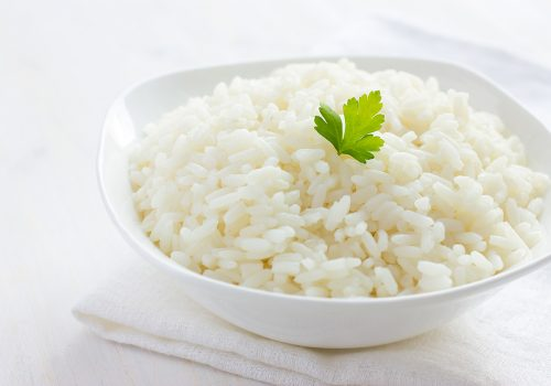 White rice in bowl on white background, selective focus